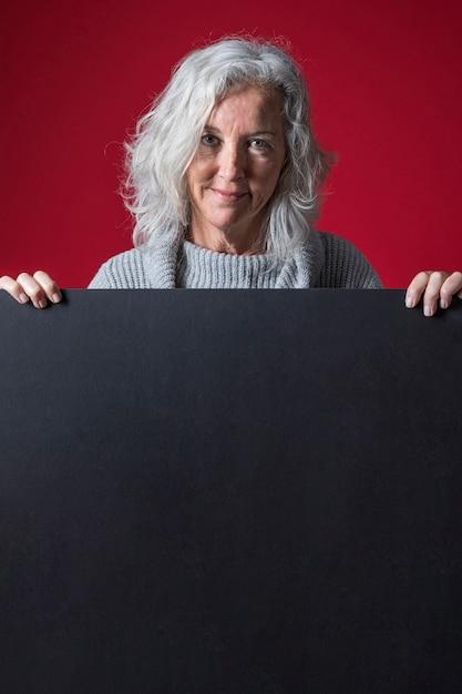 Um, mulher sênior, estar, atrás de, a, em branco, pretas, painél publicitário, contra, experiência vermelha Foto gratuita
