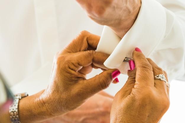 Um noivo que põe sobre botões de punho como adquire vestido em seu dia do casamento. terno do noivo Foto Premium
