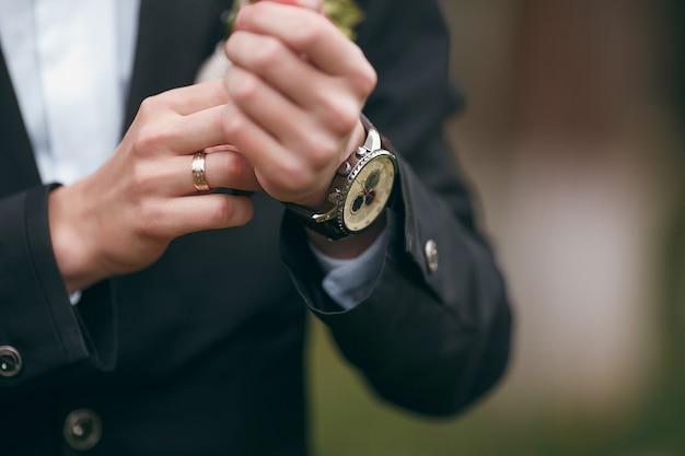 Um noivo vestindo abotoaduras enquanto se veste com roupas formais. um homem endireita as abotoaduras. terno do noivo Foto Premium