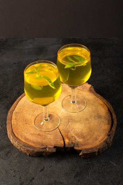 Um óculos de vista frontal com suco de suco de limão dentro de vidros transparentes na mesa de madeira marrom Foto gratuita
