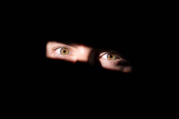 Um olhar para fora do escuro, olhos em um fundo preto Foto Premium