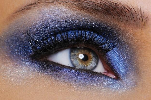 Um olho feminino com sombra azul brilhante - foto macro Foto gratuita