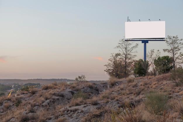 Um outdoor de publicidade vazio na montanha contra o céu Foto gratuita