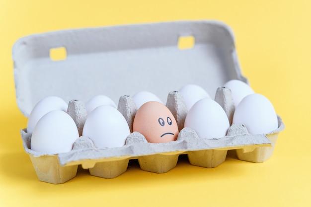 Um ovo de laranja com cara triste desenhada entre ovos brancos em uma bandeja de papelão. diferente de outro. Foto Premium