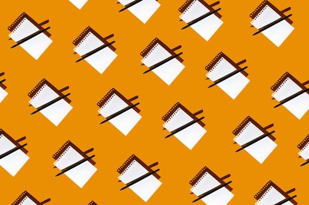 Um padrão de bloco de notas em branco, lápis preto e sombras duras sobre fundo amarelo brilhante Foto Premium