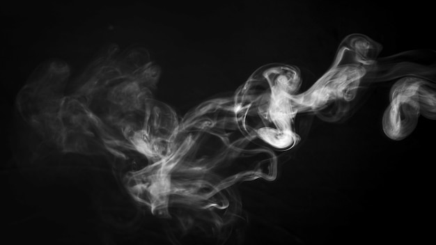 Um padrão de fumo girando grosso na frente de fundo preto Foto gratuita