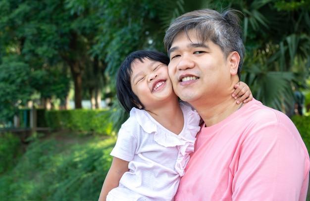 Um pai asiático está carregando uma linda filha para o peito. Foto Premium