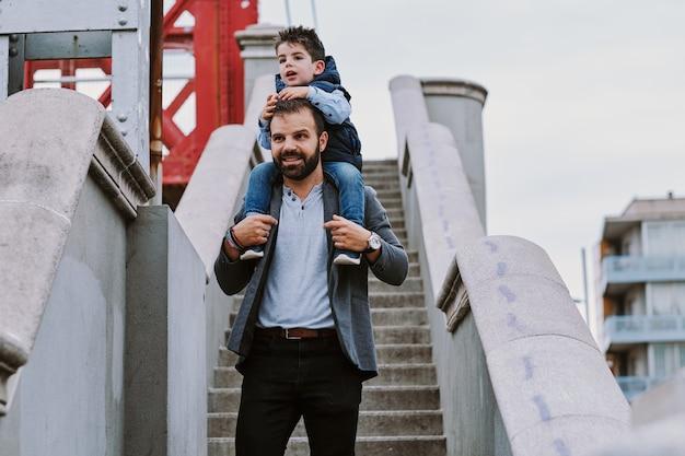 Um pai em uma escada com seu filho em um dia nublado Foto Premium
