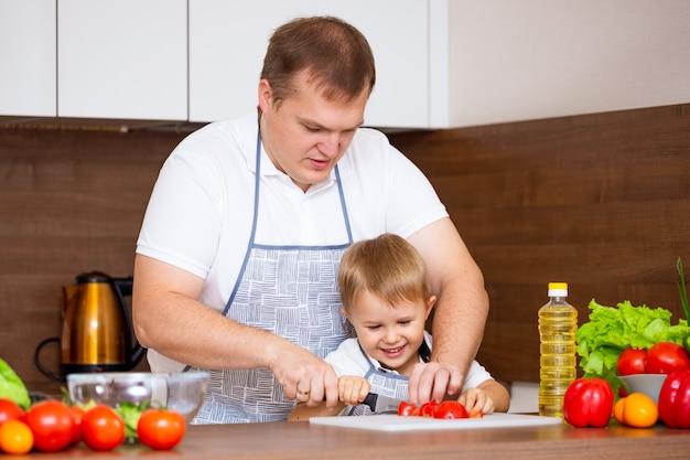 Um pai feliz e um filho pequeno preparam uma salada na cozinha com legumes. meu pai me ensina a cortar tomates no quadro-negro. conceito de dieta alimentar Foto gratuita