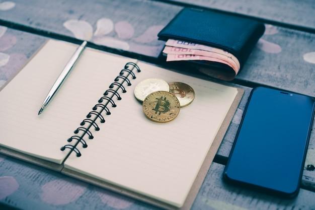 Um papel de caderno com uma caneta, moedas de ouro bitcoin e smartphone na mesa de madeira Foto Premium