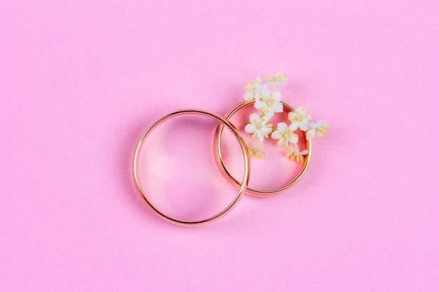 Um par de alianças de ouro e pequenas flores brancas em um anel Foto Premium
