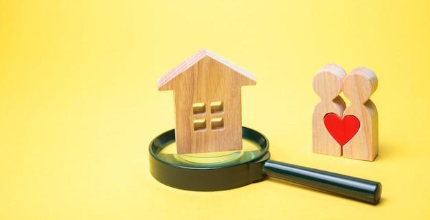 Um par de amantes está de pé perto da casa e uma lupa. Foto Premium