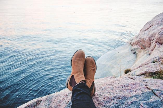 Um par de botas descansando em uma montanha em frente ao mar Foto gratuita