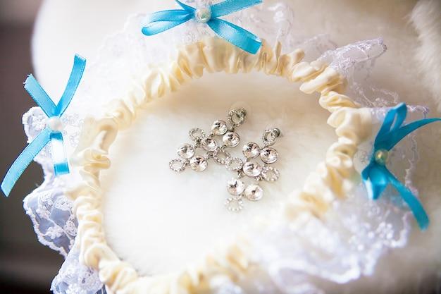 Um par de brincos de prata, liga branca com laços azuis Foto Premium