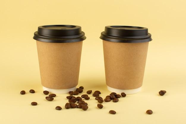 Um par de copos de café de plástico com vista frontal para entrega de café com sementes de café marrom na superfície amarela Foto gratuita