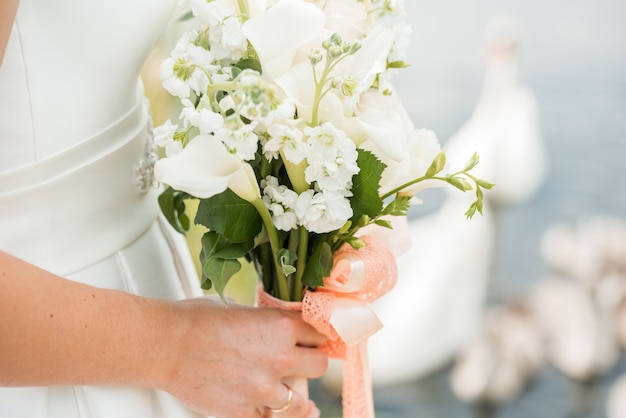 Um par de recém-casados com um buquê de rosas brancas senta-se perto do lago. cisne nada Foto Premium