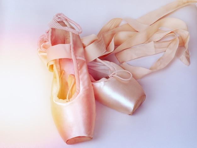 Um par de sapatilhas de ballet rosa. pointes em um branco. Foto Premium