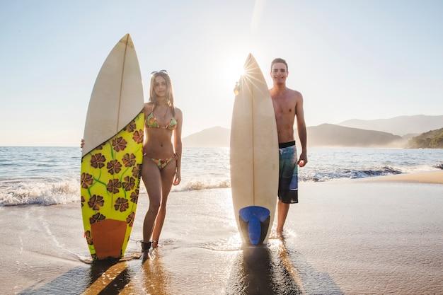 Um par de surfistas com suas pranchas de surfe Foto gratuita