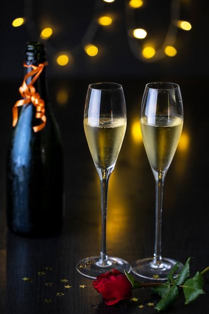 Um par de taças de champanhe com uma rosa em uma mesa e uma garrafa de champanhe. Foto Premium