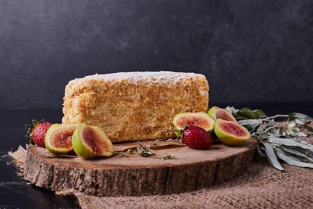 Um pedaço de bolo de napoelão em fundo escuro com figos e morangos. Foto gratuita