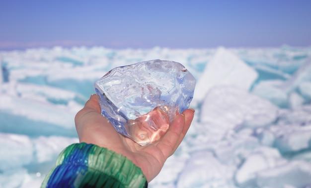 Um pedaço de gelo transparente de cristal na mão contra lago congelado em dia de sol Foto Premium