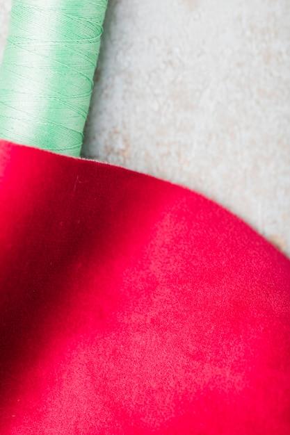 Um pedaço de tecido de costura com carretel de linha Foto gratuita