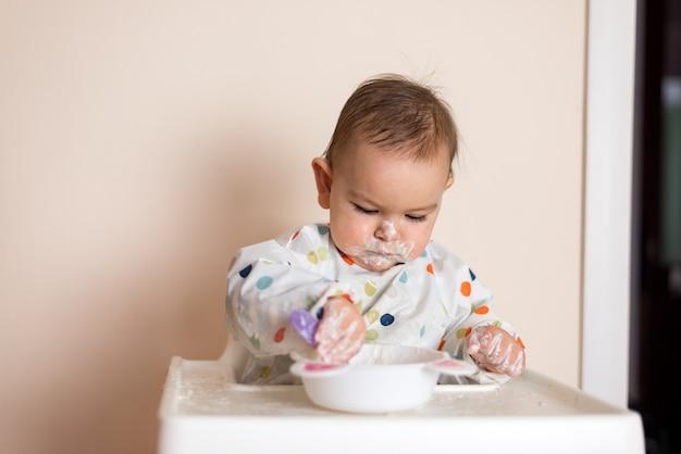 Um pequeno bebê comendo seu jantar e fazendo uma bagunça Foto Premium