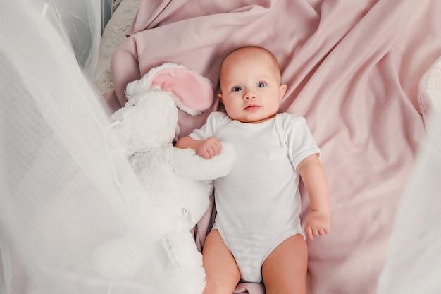 Um pequeno bebê deita em uma cama com um coelho de brinquedo e sorrisos Foto Premium