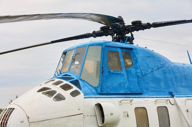 Um pequeno helicóptero branco com uma faixa azul Foto Premium
