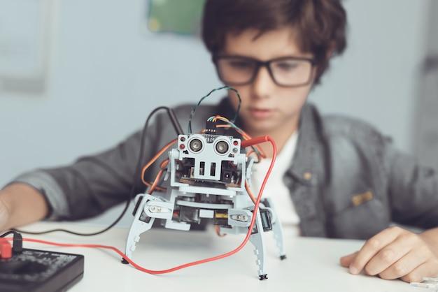 Um pequeno nerd olha atentamente para a sua criação Foto Premium