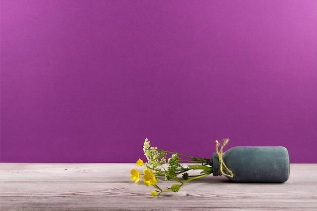 Um pequeno vaso de flores silvestres está na mesa Foto Premium