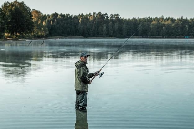 Um pescador no lago está de pé na água e pescando uma vara de pescar férias de hobby na pesca Foto Premium