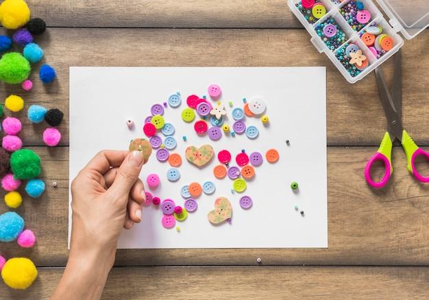 Um, pessoa, decorando, papel branco, com, coloridos, botões, sobre, tabela madeira Foto gratuita
