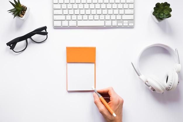 Um, pessoa, escrita, ligado, notas pegajosas, com, caneta, branco, espaço de trabalho Foto gratuita