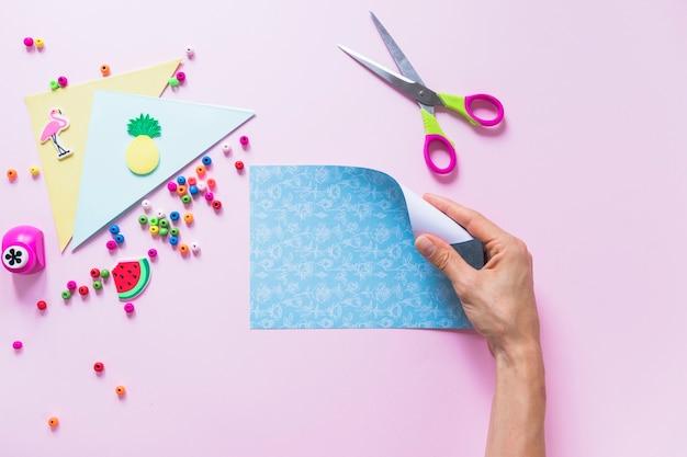 Um, pessoa, passe segurar, dobrando, papel azul, sobre, a, fundo cor-de-rosa Foto gratuita