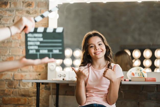 Um, pessoa, segurando, clapper, diretor, frente, menina, mostrando, polegar cima, sinal Foto gratuita