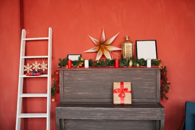 Um piano com decorações de natal e uma escada branca na casa em uma parede vermelha Foto Premium