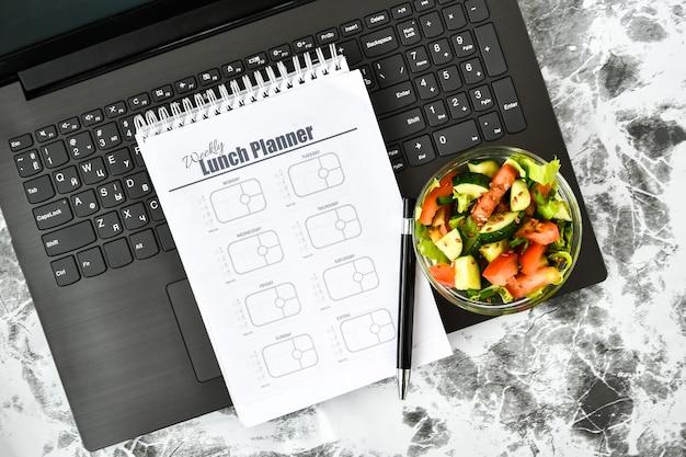 Um plano de refeições para uma semana e uma tigela com salada de legumes no local de trabalho perto do computador Foto Premium