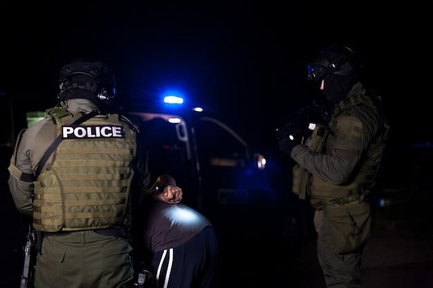 Um policial algema as mãos de um criminoso durante uma prisão. carro de polícia com faróis piscando. desfocado Foto Premium