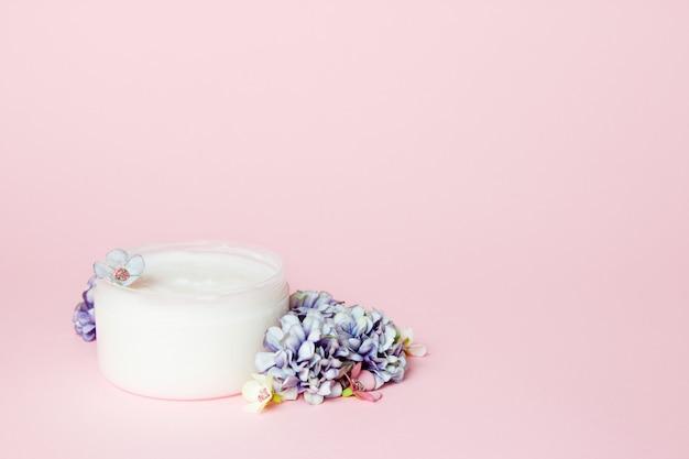 Um pote de creme com flores em rosa Foto Premium