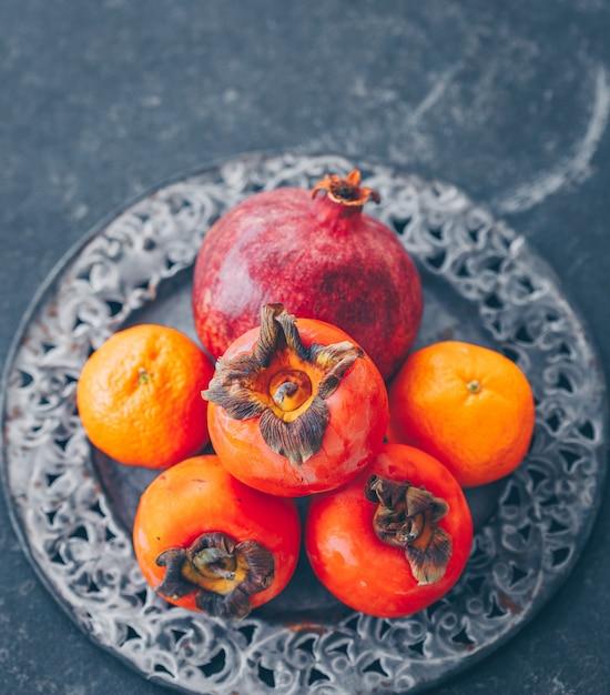 Um pouco de romã e caqui com tangerina em placa de metal na vista escura, alto ângulo. Foto gratuita