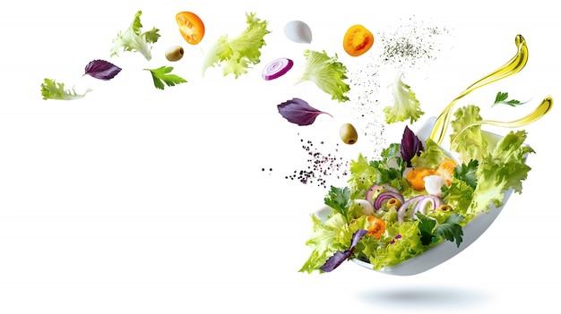 Um prato branco com salada e flutuando no ar ingredientes: azeitonas, alface, cebola, tomate, queijo mussarela, salsa, manjericão e azeite de oliva. Foto Premium
