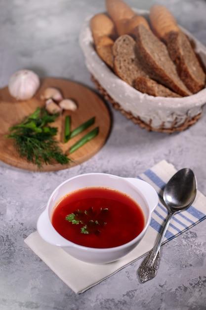 Um prato com sopa de beterraba em cima da mesa, ao lado do tabuleiro, é salsa, endro, cebola verde e alho e uma cesta com pão. almoço saboroso e saudável. Foto Premium