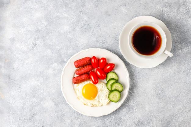 Um prato de café da manhã contendo linguiças de coquetel, ovos fritos, tomates cereja, doces, frutas e um copo de suco de pêssego. Foto gratuita