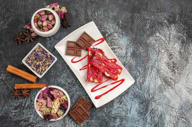 Um prato de chocolate e tigelas de flores secas ao redor em cinza Foto gratuita