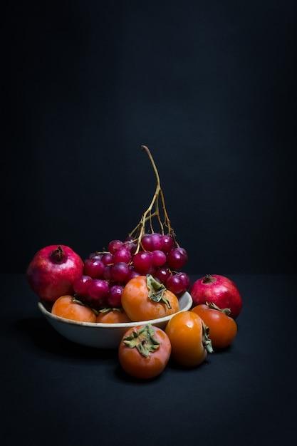 Um prato de frutas de outono em um fundo preto Foto Premium