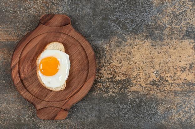 Um prato de madeira com ovo na fatia de pão branco. Foto gratuita