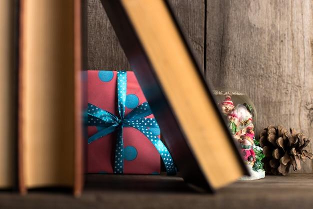 Um presente escondido em uma prateleira de madeira atrás dos livros. Foto Premium