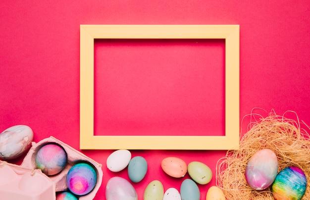 Um quadro amarelo vazio com ovos de páscoa coloridos no fundo rosa Foto gratuita