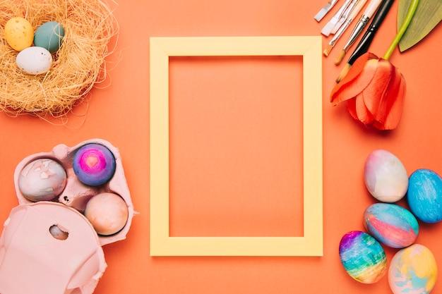 Um quadro amarelo vazio da beira cercado com ovos da páscoa; ninho; pincéis de tulipa e tinta em um fundo laranja Foto gratuita